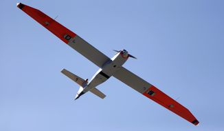 A test drone with a wing span of almost 13 feet flies over a ranch near Sarita, Texas,  Wednesday, Jan. 15, 2014. A Texas A&M Corpus Christi research team is conducting tests to help determine how unmanned aircraft system can be integrated into existing airspace. (AP Photo/Eric Gay)