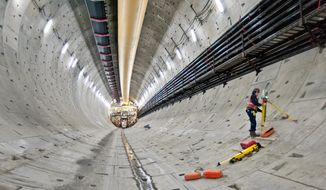 In this Dec. 6, 2013, photo provided by the Washington State Dept. of Transportation, a surveyor sets up his gear near the south end of the Highway 99 tunnel in Seattle. The next step in the process to resume drilling the highway tunnel under downtown is to get a better look at what's blocking the path of the huge boring machine called Bertha. Drilling stopped Dec. 6 after Bertha ran into a pipe. (AP Photo/Washington Dept. of Transportation)