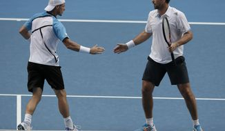 Australian players Pat Rafter, right, and Lleyton Hewitt celebrate a point win during their first round doubles match against Eric Butorac of the U.S and Klaasen Raven of South Africa at the Australian Open tennis championship in Melbourne, Australia, Wednesday, Jan. 15, 2014.(AP Photo/Rick Rycroft) -
