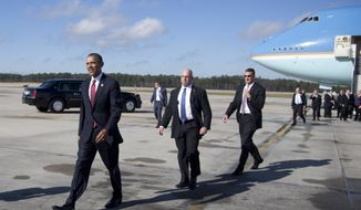 President Barack Obama walks across the tarmac to greet people as he arrives on Air Force One at Raleigh-Durham International Airport in Morrisville, N.C., Wednesday, Jan. 15, 2014, en route to North Carolina State University where he will speak about the economy. (AP Photo/Carolyn Kaster)