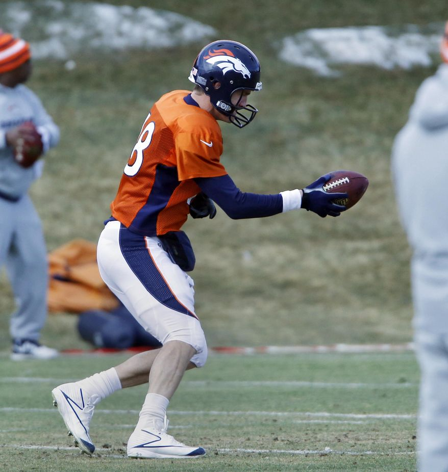 Denver Broncos quarterback Peyton Manning (18) practices handoffs at the NFL Denver Broncos football training facility in Englewood, Colo., on Wednesday, Jan. 15, 2014. The Broncos are scheduled to play the New England Patriots on Sunday for the AFC Championship. (AP Photo/Ed Andrieski)