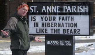 ADVANCE FOR USE SATURDAY, JAN. 18 AND THEREAFTER - In this Dec. 30, 2013, 2013 photo, Rev. Greg Jozefiak poses with one of the unique message signs he posts outside St. Anne's Catholic Church in East Moline, Ill. Jozefiak says that he loves word play and the chance to put a smile on people's faces as they drive by the church sign on the corner of 17th Avenue and 6th Street. This sign was posted following the Chicago Bears lost their bid to play in the National Football League playoffs. (AP Photo/The Dispatch, Gary Krambeck)  QUAD CITY TIMES OUT