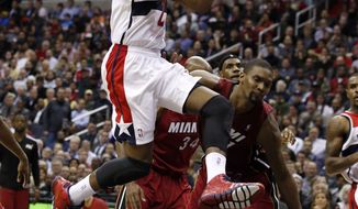 Washington Wizards guard John Wall (2) drives to the basket past Miami Heat center Chris Bosh (1) in the second half of an NBA basketball game on Wednesday, Jan. 15, 2014, in Washington. Wall had 25 points and the Wizards won 114-97. (AP Photo/Alex Brandon)
