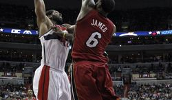 Washington Wizards forward Nene (42), from Brazil, dunks the ball over Miami Heat forward LeBron James (6) in the second half of an NBA basketball game on Wednesday, Jan. 15, 2014, in Washington. The Wizards won 114-97. (AP Photo/Alex Brandon)