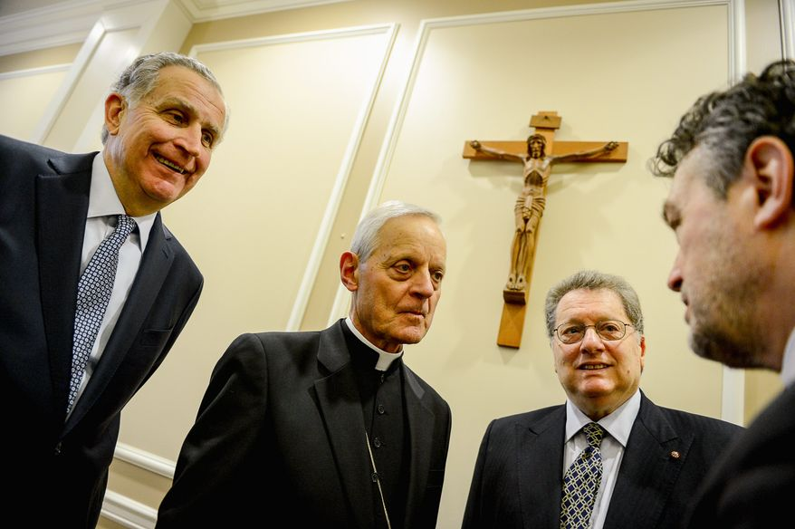 Archbishop of Washington Cardinal Donald Wuerl (second from left) speaks with Poland's Ambassador to the U.S., Ryszard Schnepf (right); conductor Gilbert Levine (second from right) and Georgetown University's Board of Directors Chairman Paul Tagliabue on Thursday after they announced a concert to celebrate the sainthood of Popes John XXIII and John Paul II in Washington in May (andrew harnik/the Washington Times)