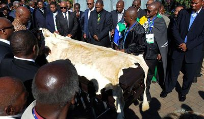 Nelson Mandela's grandson Mandla Mandela (right) watches as local chiefs drape the casket of the former South African president with a lion skin as it arrives at the Mandela residence in Qunu, South Africa, on Saturday, Dec. 14, 2013. (AP Photo/Elmond Jiyane, GCIS)