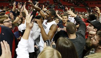 Texas Tech's Jordan Tolbert, center, is greeted by fans after a win over Baylor in an NCAA college basketball game in Lubbock, Texas, Wednesday, Jan, 15, 2014. (AP Photo/Lubbock Avalanche-Journal, Tori Eichberger) ALL LOCAL TV OUT