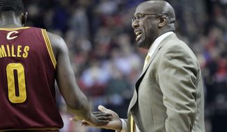 Cleveland Cavaliers coach Mike Brown, right, slaps hands with Cleveland Cavaliers guard C.J. Miles during the first half of an NBA basketball game in Portland, Ore., Wednesday, Jan. 15, 2014. (AP Photo/Don Ryan)