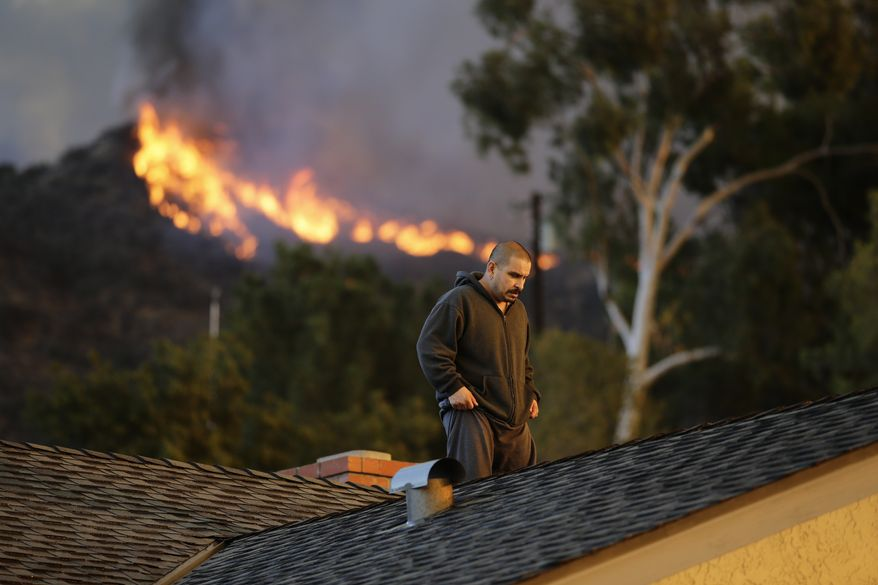 A man walks off the rooftop after spraying water on his home as firefighters battle a wildfire on Thursday, Jan. 16, 2014, in Azusa, Calif. A wildfire burned out of control near homes in the dangerously dry foothills of the San Gabriel Mountains early Thursday, fanned by gusty Santa Ana winds that spit embers into neighborhoods in the city below, igniting trees. Evacuations were ordered for houses at the edge of the fire. (AP Photo/Jae C. Hong)