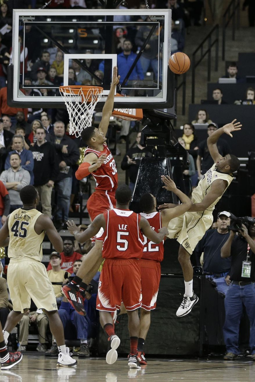 Wake Forest's Codi Miller-McIntyre (0) shoots the winning basket over North Carolina State's Kyle Washington (32) during the second half of an NCAA college basketball game in Winston-Salem, N.C., Wednesday, Jan. 15, 2014. Wake Forest won 70-69. (AP Photo/Chuck Burton)