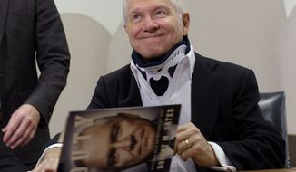 "Former Defense Secretary Robert Gates signs copies of his new book: ""Duty: Memoirs of a Secretary of War,"" during a book signing at the Pentagon, Thursday, Jan. 16, 2014. (AP Photo/Susan Walsh)"