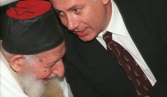 Israeli Prime Minister Benjamin Netanyahu, right, with Rabbi Yitzhak Kaduri, an influential Sephardic leader, during a Sukkot holiday gathering at the Nachalat Yitzhak synagogue in Jerusalem Tuesday Oct. 21, 1997.  U.S. peace envoy Dennis Ross is in the region holding talks with Israeli and Palestinian leaders in an effort to push peace negotiations forward.  (AP Photo/Zoom 77)