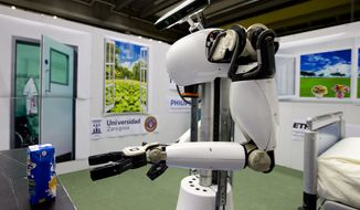 """Amigo, a white robot the size of a person, uses information gathered by other robots to move towards a table to pick up a carton of milk and deliver it to an imaginary patient in a mock hospital room at the Technical University of Eindhoven, Netherlands, Wednesday Jan. 15, 2014. A group of five of Europe's top technical universities, together with technology conglomerate Royal Philips NV, are launching an open-source system dubbed """"RoboEarth"""" Thursday. The heart of the mission is to accelerate the development of robots and robotic services via efficient communication with a network, or """"cloud"""". (AP Photo/Peter Dejong)"""