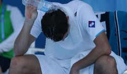 Jerzy Janowicz of Poland pours water over himself during his third round loss to Florian Mayer of Germany at the Australian Open tennis championship in Melbourne, Australia, Friday, Jan. 17, 2014.(AP Photo/Aijaz Rahi)