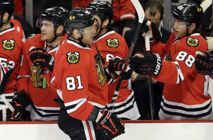 Chicago Blackhawks' Marian Hossa (81) celebrates with teammates after scoring his goal during the first period of an NHL hockey game against the Boston Bruins, Sunday, Jan. 19, 2014, in Chica