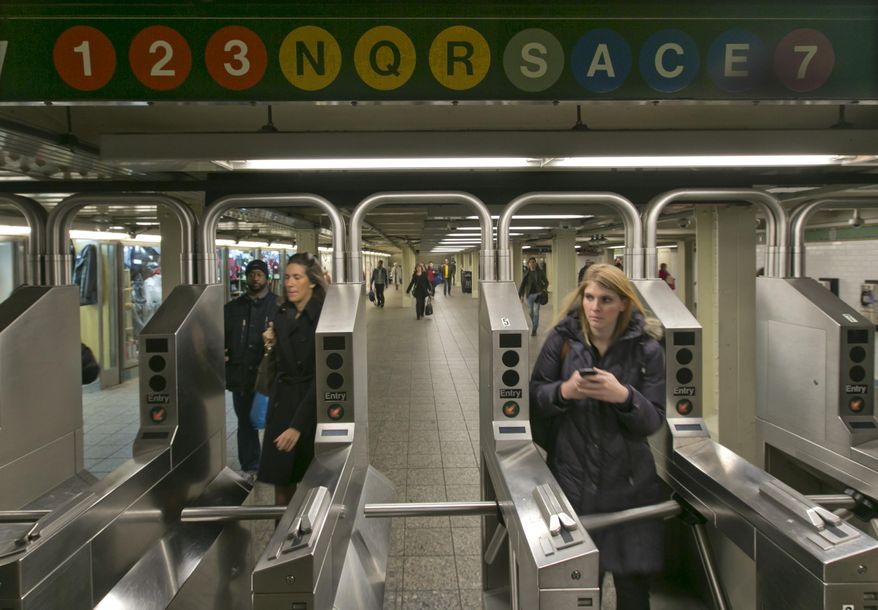 In this Dec. 4, 2013 photo, people move through the turnstiles in the subway in New York's Times Square station. Screeching subway trains emit considerable noise in a city with one of the nation's toughest noise codes. (AP Photo/Richard Drew)