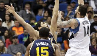 Minnesota Timberwolves' Nikola Pekovic, of Montenegro, releases a shot over Utah Jazz's Enes Kanter, of Turkey, during the first quarter of an NBA basketball game, Saturday, Jan. 18, 2014, in Minneapolis. (AP Photo/Jim Mone)