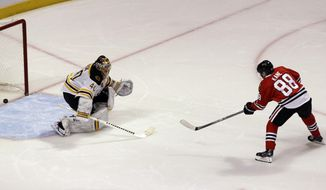 Chicago Blackhawks' Patrick Kane, right, scores against Boston Bruins goalie Tuukka Rask during the shootout of an NHL hockey game in Chicago, Sunday, Jan. 19, 2014. The Blackhawks won 3-2. (AP Photo/Nam Y. Huh)
