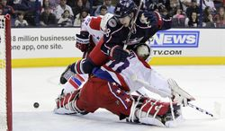 Columbus Blue Jackets' Boone Jenner, center, interferes with Washington Capitals' goalie Braden Holtby, bottom, as Capitals' Karl Azner waits for the rebound during the second period of an NHL hockey game on Friday, Jan. 17, 2014, in Columbus, Ohio. Jenner was penalized for the interference. (AP Photo/Jay LaPrete)