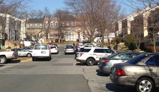 This photo taken with a cellphone camera shows police on the scene outside a home in Germantown, Md., Friday, Jan. 17, 2014, where two children were found dead and two children and an adult were found injured, hours after police had been called there for a report of a young child alone in a car. (AP Photo/Jessica Gresko)