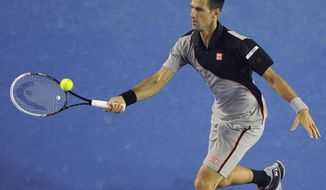 Novak Djokovic of Serbia makes a forehand return to Denis Istomin of Uzbekistan during their third round match at the Australian Open tennis championship in Melbourne, Australia, Friday, Jan. 17, 2014.(AP Photo/Andrew Brownbill)
