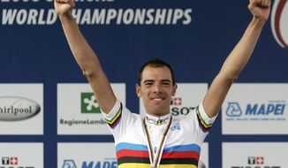 FILE - This Sept. 28, 2008 file photo shows Italy's Alessandro Ballan celebrating on the podium after winning the men's race at the road World cycling Championships, in Varese, Italy. The Italian Olympic Committee's anti-doping court announced Friday, Jan. 17, 2014 that it had banned Ballan for two years for doping after he was indicted by a general court in Mantova for alleged team-wide drug use by the Lampre team. (AP Photo/Alessandro Trovati, file)