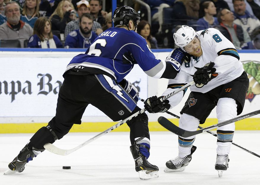 San Jose Sharks center Joe Pavelski (8) runs into Tampa Bay Lightning defenseman Sami Salo (6), of Finland, during the third period of an NHL hockey game Saturday, Jan. 18, 2014, in Tampa, Fla. The Sharks won the game 5-4. (AP Photo/Chris O'Meara)