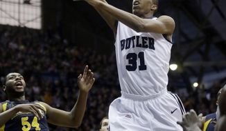 Butler forward Kameron Woods, right, shoots in front of Marquette forward Davante Gardner in the first half of an NCAA college basketball game in Indianapolis, Saturday, Jan. 18, 2014. (AP Photo/Michael Conroy)