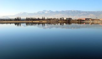 The Sierra's eastern front to the west of Reno is reflected in the Sparks Marina, where all of the fish have died over the past month _ an estimated total of 100,000 trout, bass and catfish _ on Friday, Jan. 17, 2014, in Sparks, Nev. Scientists say a sudden cold spurt in December likely caused a violent ``turnover'' of the 77-acre, man-made lake's waters that sucked out almost all the oxygen and killed the fish. (AP Photo/Scott Sonner).