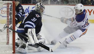 Winnipeg Jets' goaltender Ondrej Pavelec (31) stops the shot from Edmonton Oilers' Ryan Nugent-Hopkins (93) as Tobias Enstrom (39) looks on during the second period of an NHL hockey game in Winnipeg, Manitoba, Saturday, Jan. 18, 2014. (AP Photo/The Canadian Press, John Woods)