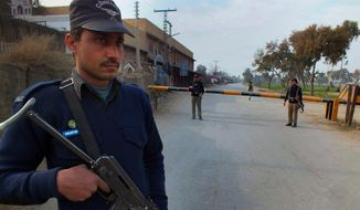 A Pakistani police officer stands guard at checkpoint on a road leading to the site of bomb explosion in Bannu, Pakistan on Sunday Jan. 19, 2014. A regular Sunday morning troop rotation going into the Pakistani tribal region of North Waziristan was shattered by an explosion that killed tens of people, mostly paramilitary troops. The Pakistani Taliban claims responsibility for placing the bomb on one of the trucks hired for the job. (AP Photo/Ijaz Muhammad)