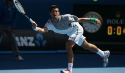 Novak Djokovic of Serbia hits a forehand return to Fabio Fognini of Italy during their fourth round match at the Australian Open tennis championship in Melbourne, Australia, Sunday, Jan. 19, 2014.(AP Photo/Aaron Favila)