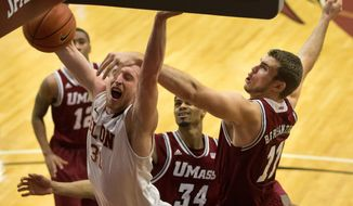 Elon forward Lucas Troutman (31) loses the ball as he is fouled by Massachusetts center Tyler Bergantino (11) during the first half of an NCAA college basketball game in Elon, N.C., Saturday, Jan. 18, 2014. (AP Photo/Lynn Hey)