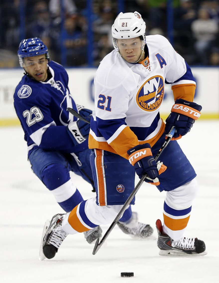 New York Islanders right wing Kyle Okposo (21) cuts around Tampa Bay Lightning right wing J.T. Brown (23) during the first period of an NHL hockey game Thursday, Jan. 16, 2014, in Tampa, Fla. (AP Photo/Chris O'Meara)