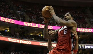 Miami Heat's LeBron James (6) is grabbed by Philadelphia 76ers' Evan Turner while going up to dunk during the first half of an NBA basketball game on Friday, Jan. 17, 2014, in Philadelphia. (AP Photo/Matt Slocum)