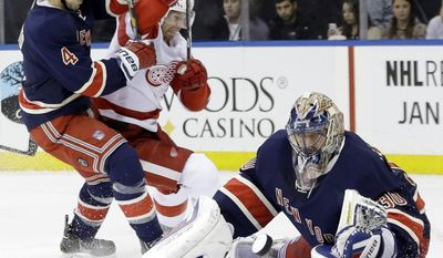 New York Rangers goalie Henrik Lundqvist (30), of Sweden, stops a shot on the goal as Detroit Red Wings' Mikael Samuelsson and Michael Del Zotto (4) fight for position during the first period of an NHL hockey game, Thursday, Jan. 16, 2014, in New York. (AP Photo/Frank Franklin II)