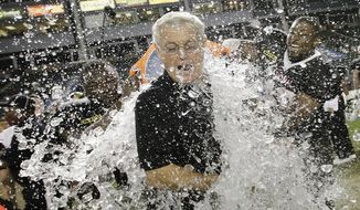 National team fullbacks J.C. Copeland, left, of LSU, and Ray Agnew, right, of Southern Illinois, dump water on coach Dick Vermeil as they celebrate the team's 31-17 win against the American team in the NFLPA Collegiate Bowl football game Saturday, Jan. 18, 2014, in Carson, Calif. (AP Photo/Jae C. Hong)