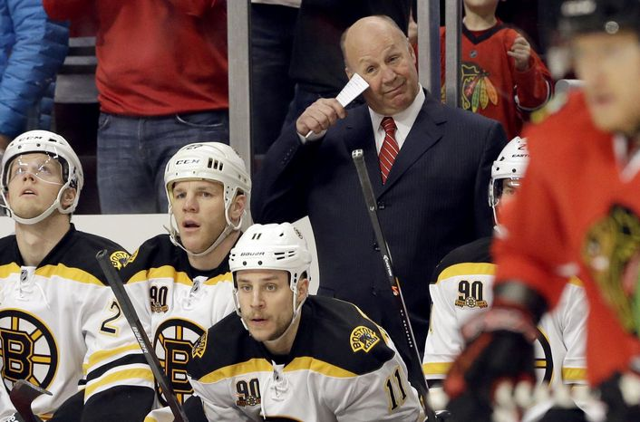 Boston Bruins head coach Claude Julien, center standing, reacts after Chicago Blackhawks' Marian Hossa scored during the first period of an NHL hockey game, Sunday, Jan. 19, 2014, in Chicago. (AP Photo/Nam Y. Huh)