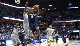 Connecticut guard Ryan Boatright (11) goes to the basket against Memphis defenders Joe Jackson (1), David Pellom, center, and Michael Dixon, Jr. (11) in the first half of an NCAA college basketball game, Thursday, Jan. 16, 2014, in Memphis, Tenn. (AP Photo/Lance Murphey)