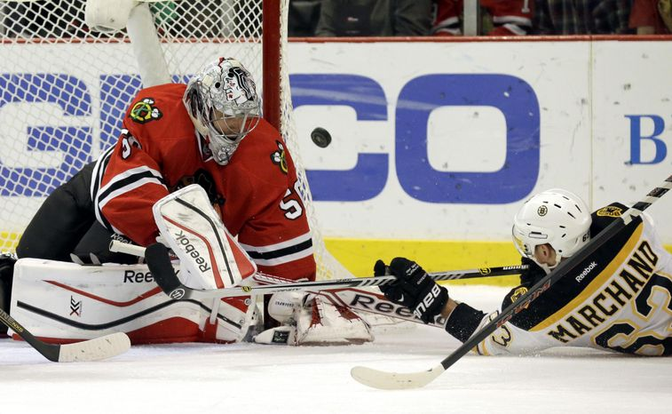 Chicago Blackhawks goalie Corey Crawford (50), left, blocks a shot by Boston Bruins' Brad Marchand (63) during the first period of an N
