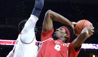 Houston's Danrad Knowles, right, gets a shot off over the defense of Louisville's Mangok Mathiang during the first half of an NCAA college basketball game, Thursday, Jan. 16, 2014, in Louisville, Ky. (AP Photo/Timothy D. Easley)