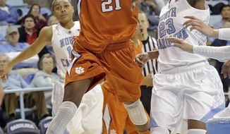 Clemson's Nikki Dixon (21) drives to the basket as North Carolina's Diamond DeShields (23) defends during the second half of an NCAA college basketball game in Chapel Hill, N.C., Thursday, Jan. 16, 2014. North Carolina won 78-55. (AP Photo/Gerry Broome)