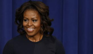 First lady Michelle Obama speaks in the Eisenhower Executive Office Building on the White House complex in Washington, Thursday, Jan. 16, 2014 . Michelle Obama is celebrating her 50th birthday Friday. The first lady was spending the day out of sight, with no scheduled public appearances after back-to-back events at the White House this week. A big birthday bash is on tap for Saturday night at the White House. President Barack Obama has been involved in planning it.  (AP Photo/Charles Dharapak)