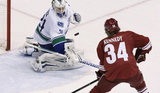 Vancouver Canucks' Eddie Lack (31) makes a save on a shot by Phoenix Coyotes' Tim Kennedy (34) during the second period of an NHL hockey game on Thursday, Jan. 16, 2014, in Glendale, Ariz. (AP Photo/Ross D. Franklin)