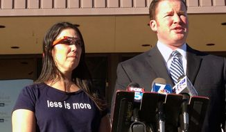 Cecilia Abadie, left, wears a Google Glass computer-in-eyeglass device while her attorney, William Concidine, speaks to the media, Thursday, Jan. 16, 2014 in San Diego. A  San Diego traffic court threw out a citation Thursday against Abadie, a woman believed to be the first motorist in the country ticketed for driving while wearing a Google Glass computer-in-eyeglass device. (AP Photo/U-T San Diego, John Gastaldo)  NO SALES; COMMERCIAL INTERNET OUT