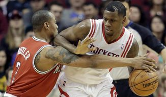 Milwaukee Bucks' Caron Butler, left, tries to steal the ball from Houston Rockets' Terrence Jones during the second quarter of an NBA basketball game, Saturday, Jan. 18, 2014, in Houston. (AP Photo/David J. Phillip)