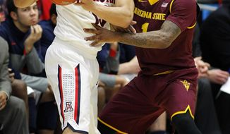 Arizona's Nick Johnson, left, looks to pass against Arizona's State's Jahil Carson during the second half of an NCAA college basketball game Thursday, Jan. 16, 2014, in Tucson, Ariz. Arizona won 91-68. (AP Photo/John MIller)