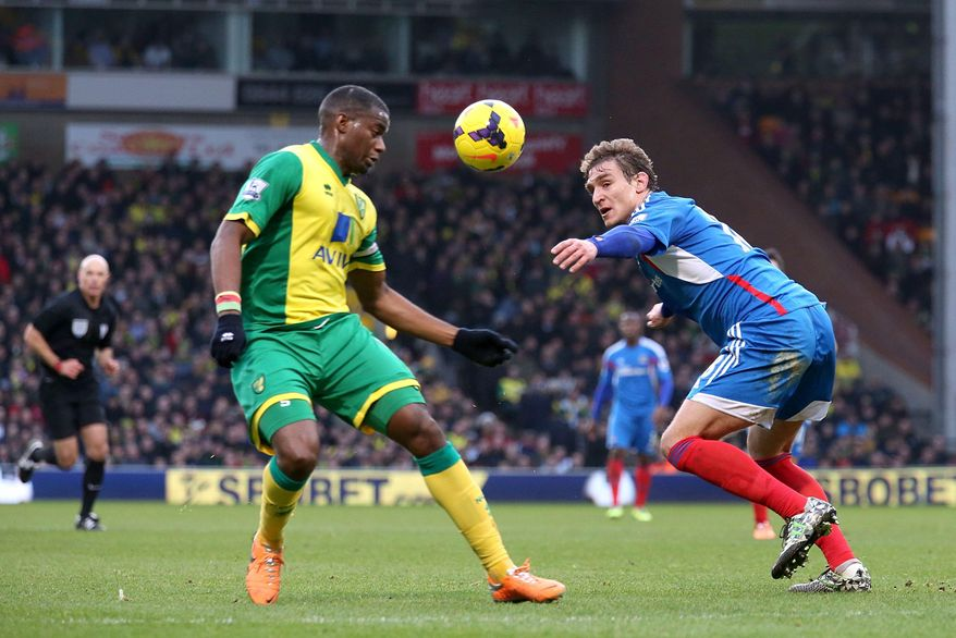 Norwich City's Sebastien Bassong, left, and Hull City's Nikica Jelavic battle for the ball during their English Premier League soccer match at Carrow Road, Norwich, England, Saturday, Jan. 18, 2014. (AP Photo/Chris Radburn, PA Wire)   UNITED KINGDOM OUT  -  NO SALES  -  NO ARCHIVES