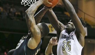 Vanderbilt forward James Siakam (35) blocks a shot by Missouri guard Earnest Ross (33) in the first half of an NCAA college basketball game, Thursday, Jan. 16, 2014, in Nashville, Tenn. (AP Photo/Mark Humphrey)