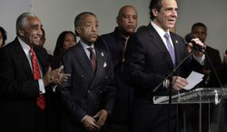 New York Gov. Andrew Cuomo, right, speaks during his appearance at Sharpton's National Action Network headquarters, in New York,  Saturday, Jan. 18, 2014. Standing at left is U.S. Rep. Charles Rangel, D-NY, and the Rev. Al Sharpton, second left. (AP Photo/Richard Drew)